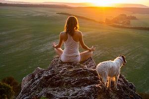 Meditating with dog at sunset